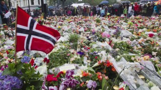 People gather to offer flowers in tribute to the victims of Friday's twin attack in Oslo outside the cathedral of Oslo