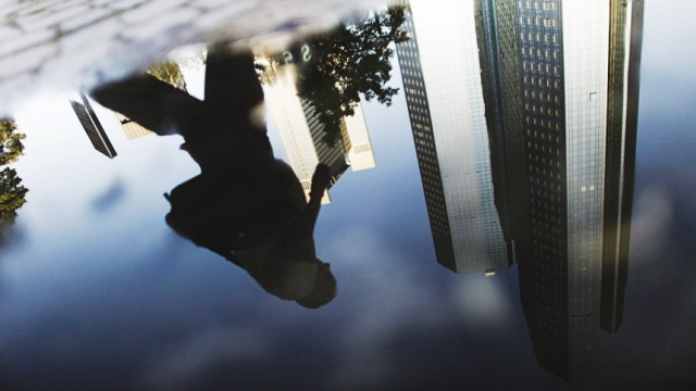 Headquarters of Deutsche Bank are reflected in a puddle in Frankfurt
