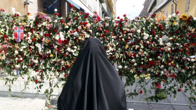 A Muslim woman stands in front of a sea of floral tributes placed outside the Oslo Cathedral