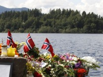 Flowers and Norwegian flags are seen at a temporary memorial site on the shore in front of Utoeya island