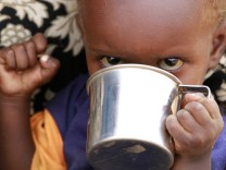 A newly arrived refugee child drinks at the Baley settlement near the Ifo extension refugee camp in Dadaab, near the Kenya-Somalia border