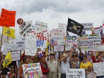 People hold signs during a 'tea party' protest in Flagstaff, Arizona