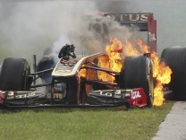 Renault Formula One driver Nick Heidfeld of Germany tries to leave his burning car during the Hungarian F1 Grand Prix at the Hungaroring circuit near Budapest