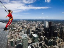 A reporter leans over the edge of the catwalk during the media preview for the 'EdgeWalk' on the CN Tower in Toronto