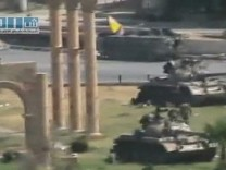Armoured vehicles are seen stationed in the city of Hama in this still image taken from video posted on a social media website