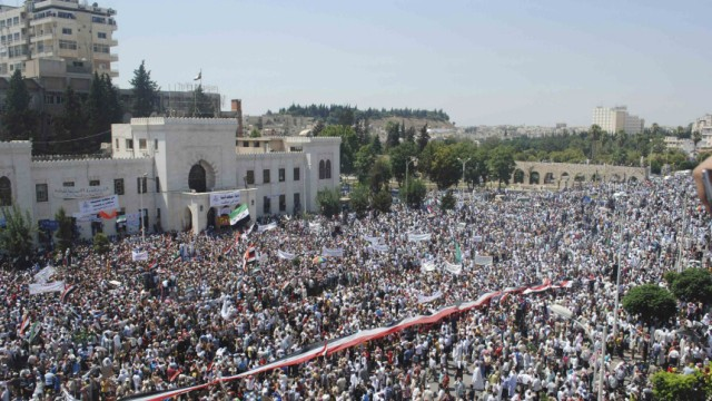 A giant Syrian flag is held by the crowd during a protest against President Bashar al-Assad after Friday prayers in the city centre of Hama