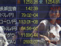 A woman is reflected on a board displaying the current Japanese yen's exchange rate against the U.S. dollar outside a brokerage in Tokyo