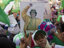 A woman gestures near a picture of Libyan leader Muammar Gaddafi during a pro-government rally in Tripoli