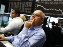 A trader reacts in front of the DAX index board at Frankfurt's stock exchang