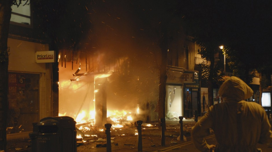 A bystander looks at a blazing store after looters rampaged through a shopping mall in Woolwich, southeast London
