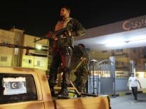 Rebel fighters stand guard outside Al-Galah hospital in Benghazi