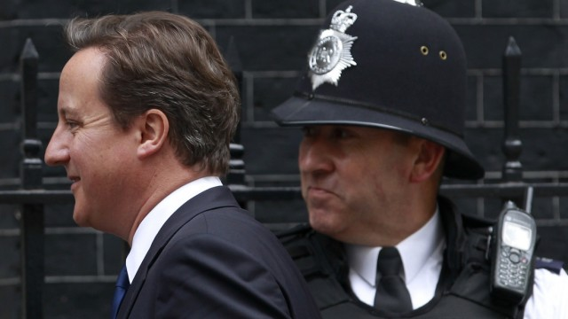 Britain's Prime Minister Cameron walks past a police officer outside 10 Downing Street in London