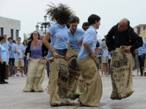 A monk joins a group of French pilgrims in a sack race in Oviedo