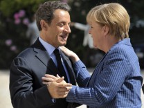 Nicolas Sarkozy welcomes Angela Merkel as she arrives for a meeting at the Elysee Palace in Paris