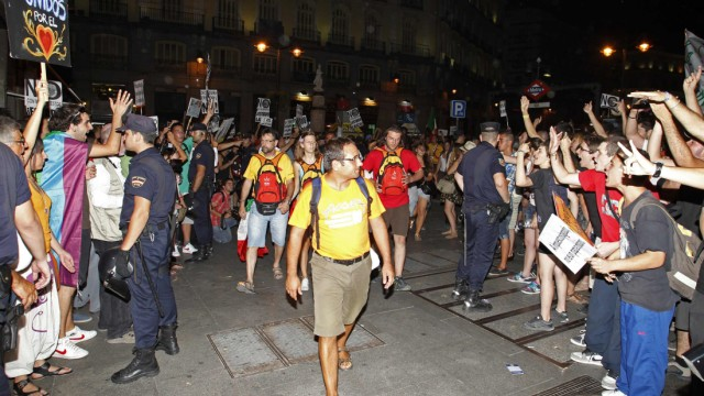 Protesters shout at pilgrims during a demonstration against the cost of the papal visit in Madrid