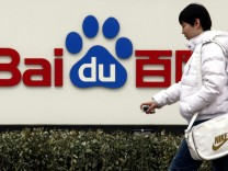 File photo of pedestrian walking past the company logo of Baidu located outside their headquarters in Beijing