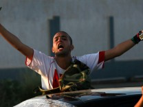 Libyan rebel fighters ride through the town of Maia celebrating after advancing to the outskirts of Tripoli