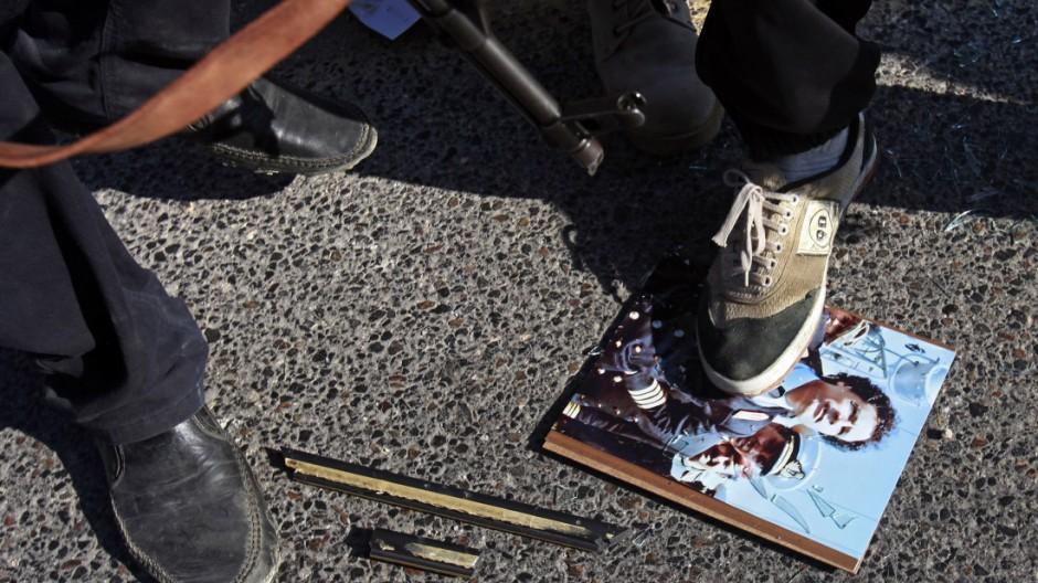 Diktator im Dreck: ein libyscher Rebell tritt in Tripolis auf ein Foto des Noch-Diktators.