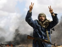 File photo of a rebel fighter shouting in front of a burning vehicle between Benghazi and Ajdabiyah