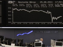 A trader stands under the DAX index board at Frankfurt's stock exchange