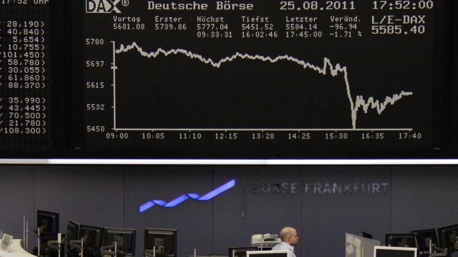 A trader stands under the DAX index board at Frankfurt's stock exchange