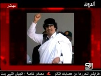 A still image of Libyan leader Muammar Gaddafi is displayed to accompany his audio message broadcast by Syrian TV channel Al-Orouba