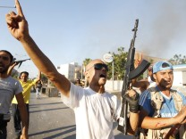 Libyan rebel fighters celebrate after pushing back Muammar Gaddafi's forces in Abu Salim district in Tripoli