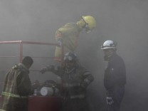 Firefighters stand amidst smoke coming out from a building housing a casino after an attack in Monterrey