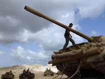 A rebel fighter walks on top of a T-55 tank in Misrata