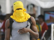 Bolt of Jamaica covers his head with a shirt during a training session at the IAAF World Championships in Daegu
