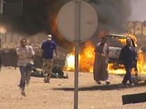 Rebellen setzen einen Truck nahe Sirte in Brand und nehmen anschließend zwei Gaddafi-Anhänger fest.