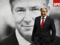 Berlin Mayor Wowereit poses in front of his election poster after it was unveiled to journalists in Berlin