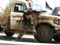 A rebel fighter fires his machine gun towards a sniper from a hotel where foreign journalists are staying at in Tripoli