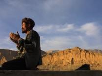 Muslim beim Gebet vor zerstörter Buddha-Statue