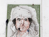 A bullet-riddled portrait of Muammar Gaddafi is seen on the wall of a building in Tripoli
