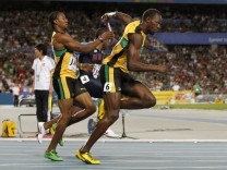 Usain Bolt of Jamaica takes the baton from teammate Yohan Blake on his way to winning the men's 4x100 metres relay with a world record time in Daegu