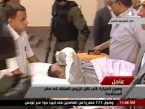 Video grab of ousted Egyptian president Mubarak being wheeled into the courtroom on a stretcher in Cairo