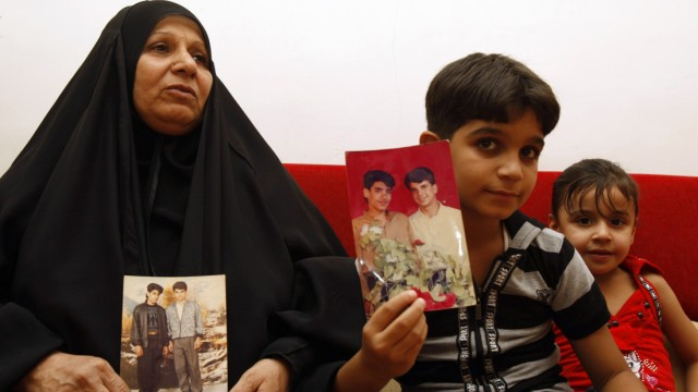 The mother and son of Baha Mousa (R in the picture), an Iraqi hotel receptionist who was kicked and beaten to death whilst in British Army custody, hold pictures of him at their house in Basra