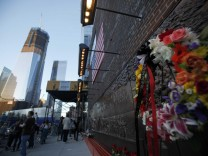 A flower wreath leans against the memorial wall at New York City Firehouse #10, which is directly across from Ground Zero and the new World Trade Center building, in New York