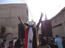People protest against President Bashar al-Assad on the first day of Eid Al-Fitr in the city of Suqba