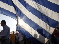Taxi drivers stand near a huge Greek flag during a protest outside the parliament in Athens