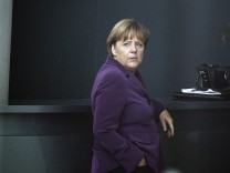German Chancellor Merkel is seen through a window of Chancellery as she waits for arrival of Finnish Prime Minister Katainen in Berlin