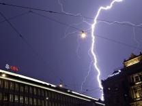 Lightning strikes over the headquarters of Swiss banks UBS and Credit Suisse during a thunderstorm over the Paradeplatz square in Zurich
