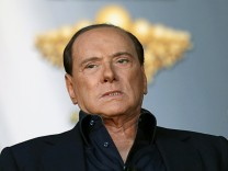 Italy's Prime Minister Berlusconi looks on as he attends the Atreju political meeting in Rome