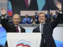 Russia's President Medvedev and Prime Minister Putin wave to supporters during the United Russia congress in Moscow