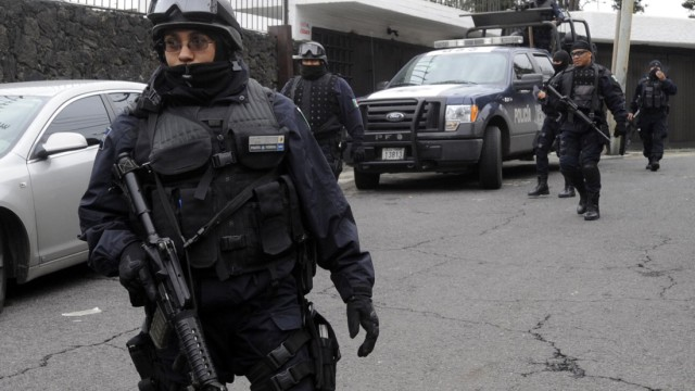 Federal police officers block access to a street during a raid at a house in Mexico City