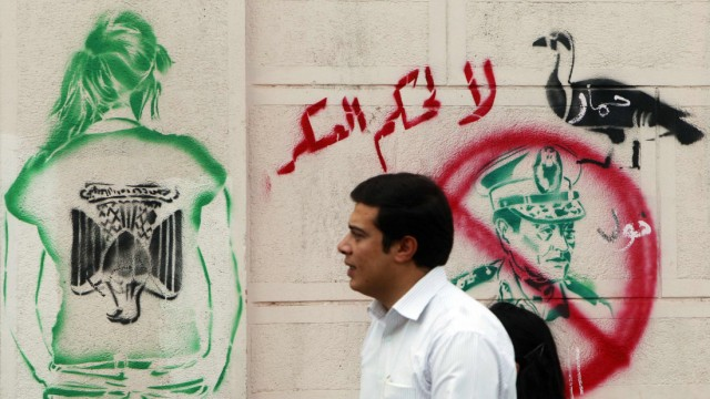 A man walks past a graffiti depicting Field Marshal Mohamed Tantawi in downtown Cairo