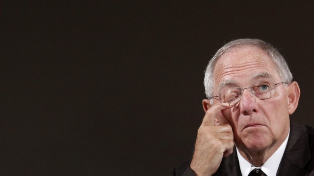 German Finance Minister Schaeuble wipes face during International Meeting of Prayer for Peace in Munich