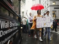 Demonstrators from the Occupy Wall Street campaign march past the entrance of a subway station in New York