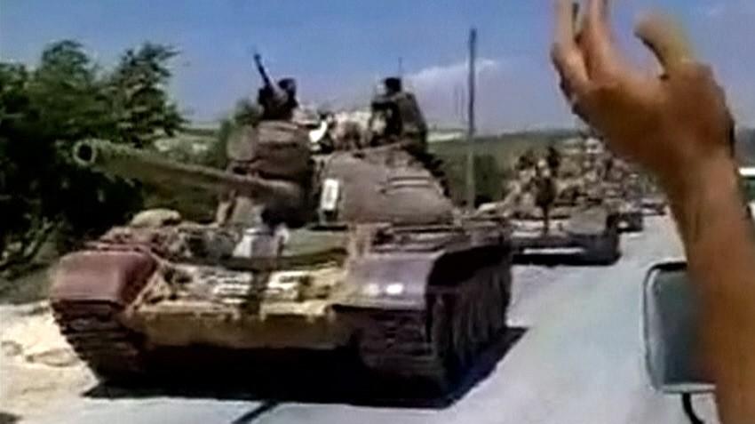 Military tanks drive into the Jabal Al-Zawya area of Idlib